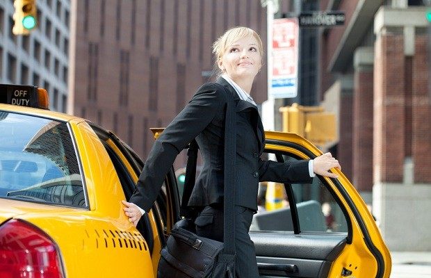 Business woman traveling by yellow taxi in city