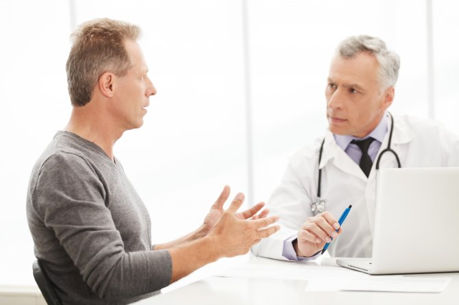 Older-male-doctor-with-laptop-talking-to-middle-age-male-patient