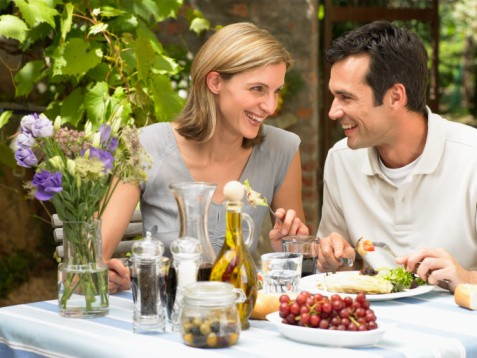 Couple sitting at outdoor table eating meal, smiling