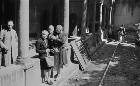 Luigi Ferrario. Via San Gregorio, nel chiostro del Lazzaretto, tre donne accusate di collaborazionismo rasate a zero e sorvegliate da un partigiano armato di moschetto.
