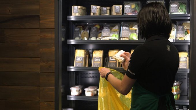 Una commessa Starbucks prepara il sacchetto per il Food Share