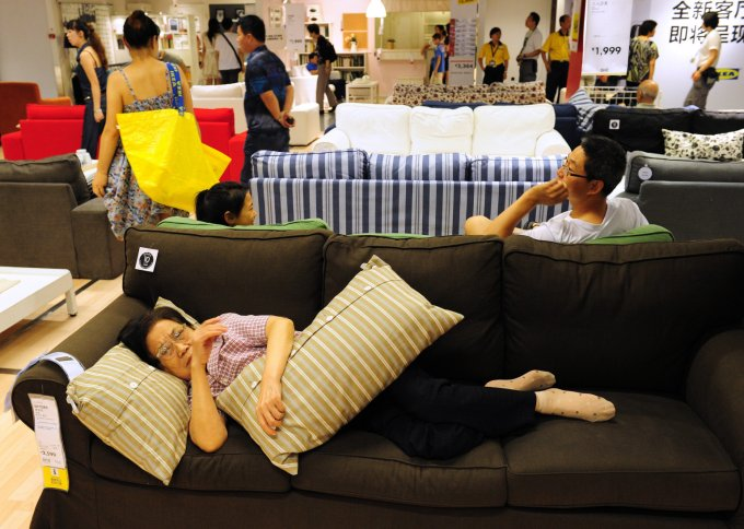 An elderly Chinese (bottom) women rests on a sofa as people shop at an Ikea frurniture store in Beijing on August 15, 2011. Asia, including China and India, will be vulnerable if the US and Europe slip into another recession, Singapore Prime Minister Lee Hsien Loong said in his annual policy speech, Lee warned it was possible the world would sink into another recession because of the debt crisis in Europe and the United States' economic woes that led to a landmark downgrade by Standard & Poor's of the country's top-notch credit ratings. AFP PHOTO / Mark RALSTON (Photo credit should read MARK RALSTON/AFP/Getty Images)