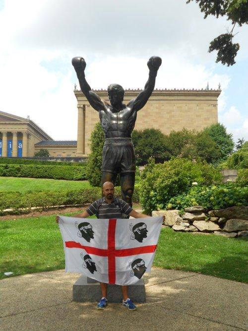 Un viaggiatore sardo con la bandiera sotto la statua di Rocky a Philadelphia